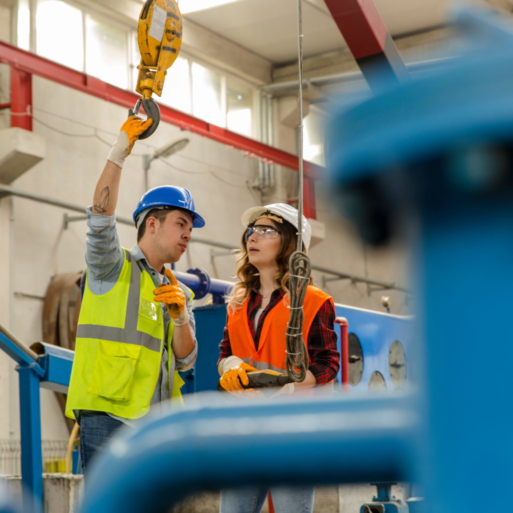Young heavy industry worker businessman and engineer woman holding crane hook button working with safety workwear and moving a massive metal construction object in warehouse of factory